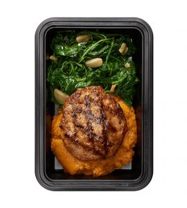 Clean Burger: A lean homemade turkey burger over creamy mashed sweet potatoes served with a side of sautéed garlic spinach.