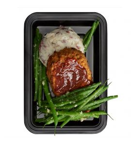 "Lentil Meatloaf: A flavor-packed homemade lentil ""meatloaf"" patty topped with our famous BRO-BQ sauce, served with a side of creamy parmesan mashed potatoes and garlic green beans."